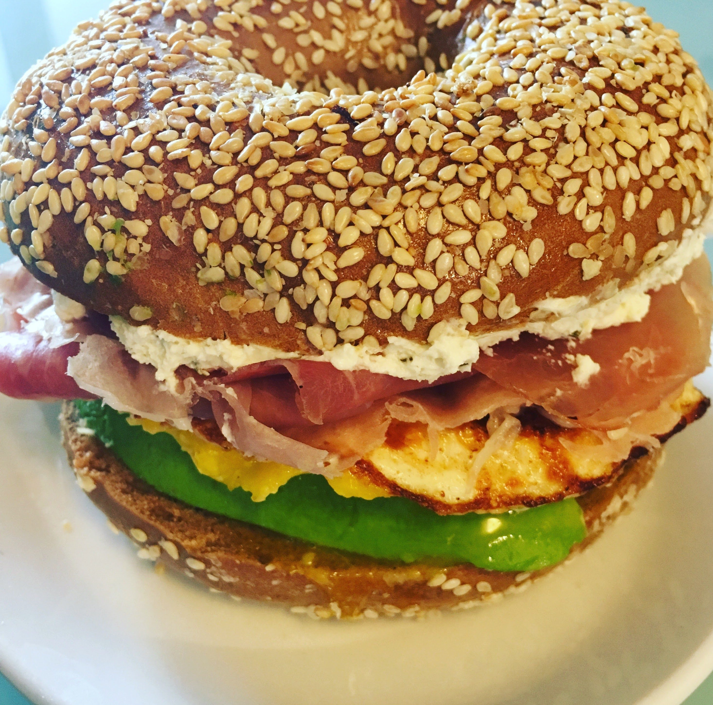 Pumpernickel Sesame Seed Bagel with Prosciutto, Fried Egg, Avocado and Whipped Cream Cheese and Chives